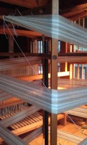 Winding a new warp on a vertical warping mill.