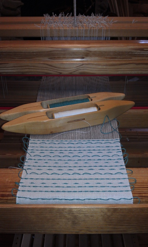 Woven shibori, with pattern threads in teal.