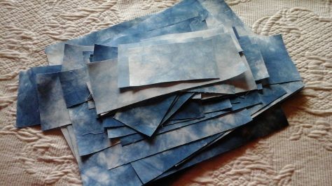 Growing stack of indigo dyed swatches.